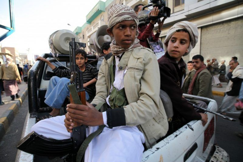 Boys who are part of the Houthi fighters hold weapons as they ride on the back of a patrol truck in Sanaa March 13, 2015. REUTERS/Mohamed al-Sayaghi