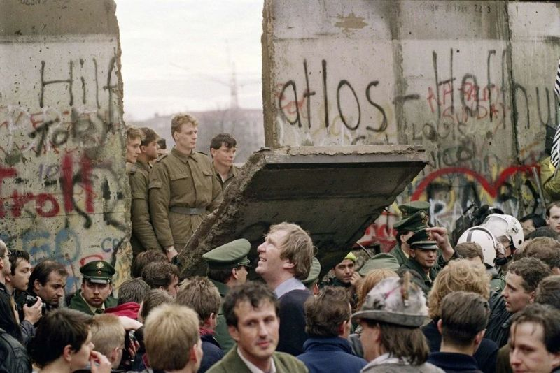 West Berliners watching East German border guards open up a section of the Berlin Wall on Nov. 11, 1989. Credit Gerard Malie/Agence France-Presse — Getty Images
