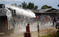 The police firing water cannons and tear gas at protesters in Bujumbura on Sunday. Credit Thomas Mukoya/Reuters
