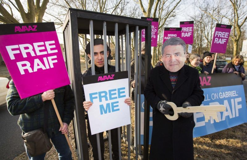 Activists of the global civic movement Avaaz dressed as Saudi Blogger Raif Badawi and Germany's Minister of Economic Affairs, Sigmar Gabriel, right, demonstrate in front of the military airport of Tegel Berlin, Germany, Friday, March 7, 2015. (Gero Breloer/Ap Images For Avaaz)