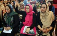 Executive Director for Afghan women's Network (AWN), Hasina Safi, center, raises her hand to ask a question during a press conference by Amnesty International. (Massoud Hossaini/AP)