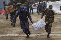 Nepali soldiers and policemen run with parcels of food aid during relief operations following the April 25 earthquake. (Roberto Schmidt/Agence France-Presse/Getty Images)
