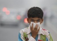 A child tries to protect himself from the air pollution in New Delhi. Credit Sanjeev Verma/Hindustan Times, via Getty Images
