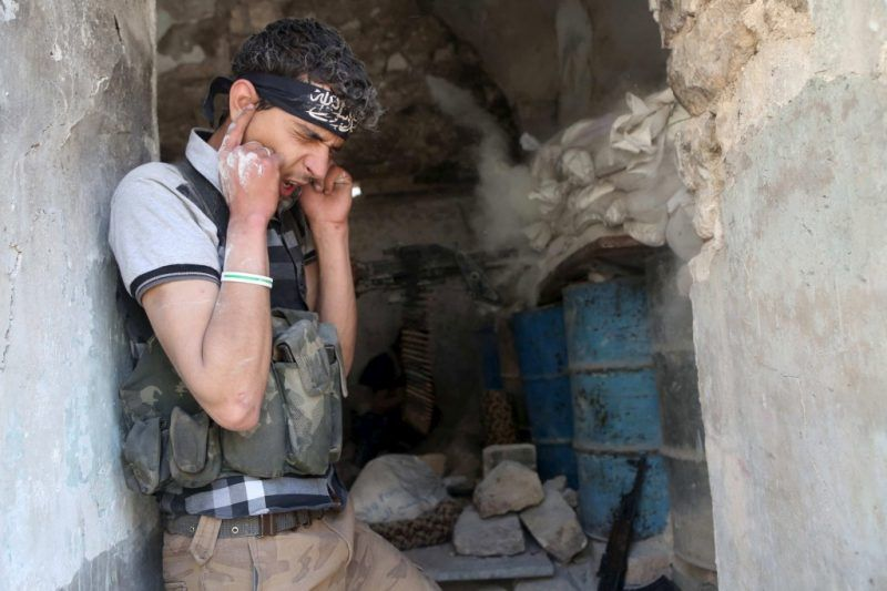 A Free Syrian Army fighter covers his ears as his fellow fighter fires a weapon during clashes with forces loyal to Syria's President Bashar al-Assad in Aleppo, April 30, 2015. REUTERS/Hosam Katan