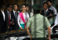 Burma opposition leader Aung San Suu Kyi, fourth from left, arrives at Beijing Capital International Airport on June 10. (Mark Schiefelbein/Associated Press)