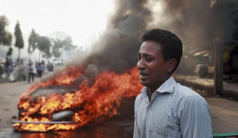 A Bangladeshi man cries after his vehicle was set on fire by Islamist party Jamaat-e-Islami activists following the execution of their party leader Abdul Quader Mollah in Dhaka, Bangladesh, Friday, Dec. 13, 2013. (AP Photo/Suvra Kanti Das).