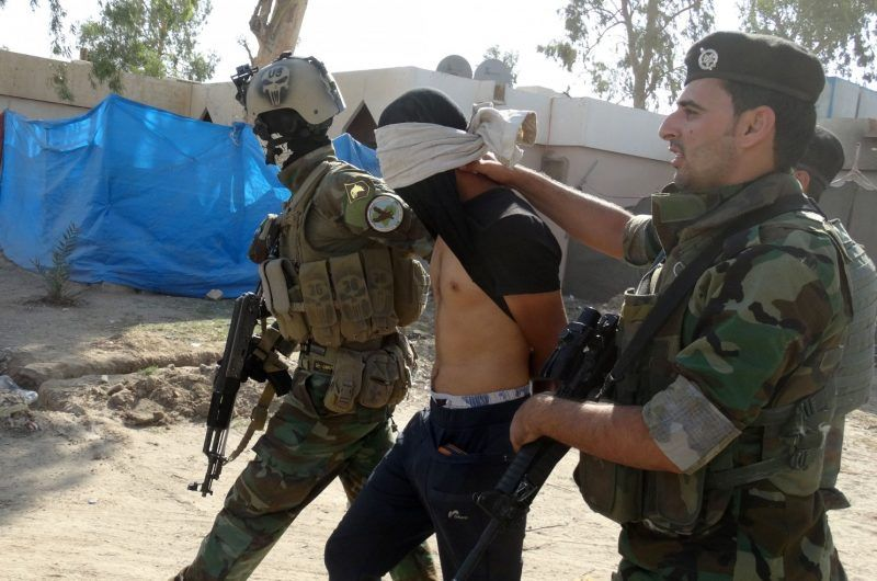 In this Thursday, June 18, 2015 file photo, Iraqi security forces arrest a suspect accused of being a militant of the Islamic State group, at a refugee camp in Habaniyah, 80 kilometers (50 miles) west of Baghdad, Iraq. (Uncredited/AP)