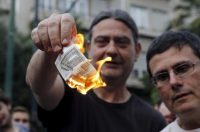 Anti-austerity protesters burn a euro note during a demonstration outside the European Union (EU) offices in Athens, Greece June 28, 2015. REUTERS/Alkis Konstantinidis