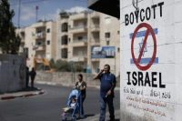 Palestinians walk past a sign in Bethlehem that calls for a boycott of Israeli products coming from Jewish settlements. (Thomas Coex/Agence France-Presse via Getty Images)
