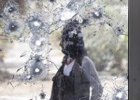 A southern resistance fighter is pictured through a damaged door glass as he stands guard at the international airport of Yemen's southern port city of Aden, July 24, 2015. REUTERS/Faisal Al Nasser