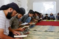 Members of Ahrar al-Sham take Koran lessons inside a camp on July 7 during the holy month of Ramadan in Idlib countryside, Syria. (Ammar Abdullah/Reuters)