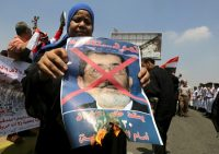 A woman burns a portrait of ousted President Mohamed Mursi at the funeral of Egyptian public prosecutor Hisham Barakat, on the second anniversary of the June 30 protests, in Cairo, Egypt, June 30, 2015. REUTERS/Mohamed Abd El Ghany