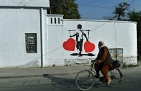 An Afghan rides past a painting aimed to combat corruption in Kabul. (Wakil Kohsar/AFP/Getty Images)
