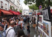 Tourists look at the work of painters in Place du Tertre in the Montmartre district of Paris on August 16, 2015. (Patrick Kovarik / AFP/Getty Images)