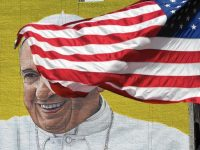 A U.S. flag blows in the wind in front of a mural of Pope Francis, located across the street from Madison Square Garden in New York City, on Sept. 21. The city is preparing for the religious leader's visit this week. (Timothy A. Clary / AFP/Getty Images)