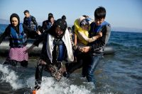 Migrants arriving from Turkey by dinghy landing Friday on the Greek island of Lesbos. Credit Petros Giannakouris/Associated Press