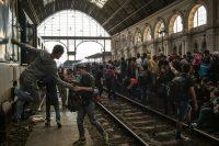 Emigrantes de Siria y Afganistán tratando de abordar un tren en Hungria con destino a Alemania. Credit Mauricio Lima para The New York Times.