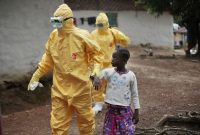Nine-year-old Nowa Paye is shown last year being taken to an ambulance in her village in Liberia after showing signs of the Ebola infection. (Jerome Delay/Associated Press)