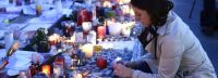 A woman lights a candle at a makeshift memorial at the Place de la Republique in Paris on November 23, 2015 in tribute to the victims of the November 13 terror attacks in Paris. A coordinated wave of attacks on Parisian nightspots claimed by Islamic State group (IS) jihadists killed 130 people. AFP PHOTO / ERIC FEFERBERG