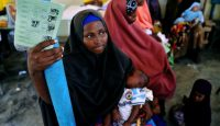 A Somali mother holding a medical card waits for her baby to be given a pentavalent vaccine injection at a medical clinic in Mogadishu. Photo by Getty