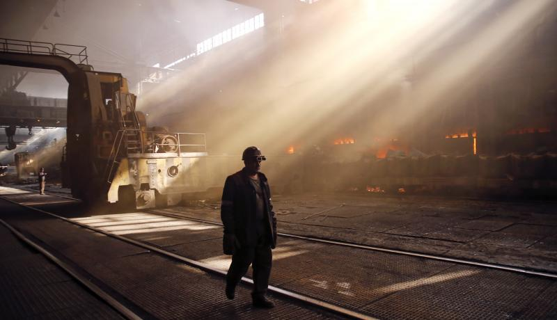 An employee walks through the scrap metal area at the Zaporizhstal steel plant in Ukraine on 14 October 2013. Photo via Getty Images.