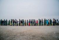 Migrantes de Siria, Iraq y Afganistán haciendo fila para recibir alimentos en Grecia. Credit Tomas Munita para The New York Times