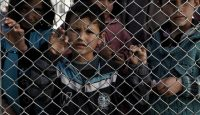 Migrant children stand behind a fence at the Moria reception centre in Mytilene on 23 February 2016. Photo by Getty Images.