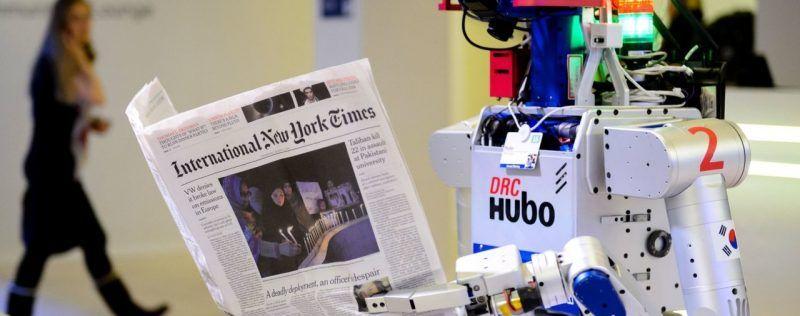 Robot tenant un journal lors d'une démonstration au World Economic Forum. © AFP / FABRICE COFFRINI