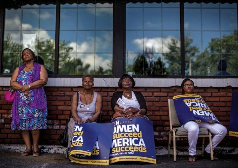 """Women listen to lawmakers speak about equal pay during a """"When Women Succeed, America Succeeds"""" bus tour stop in Ohio in 2014. (Melina Mara/The Washington Post)"""