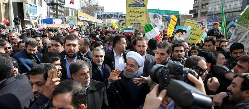 Iranian President Hassan Rouhani waves as he arrives to attend a ceremony marking the 37th anniversary of the Islamic Revolution, in Tehran's Azadi Square, February 2016.