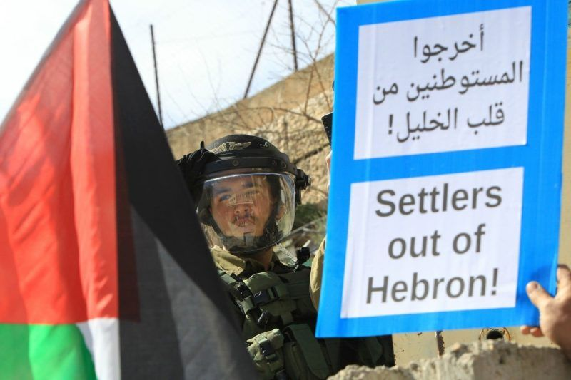 An Israeli soldier stands behind a Palestinian flag and a placard held by a protester during a Feb. 20 demonstration against Jewish settlements in the West Bank city of Hebron. (Hazem Bader/Agence France-Presse via Getty Images)