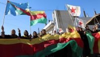 Kurdish women hold flags and banners of the PYD during a demonstration against the exclusion of Syrian Kurds from the Geneva talks on 4 February 2016. Photo by Getty Images.