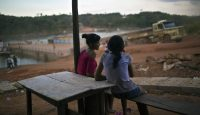 Girls look on as a logging truck disembarks from a ferry in the Amazonian state of Para, Brazil. Photo via Getty Images.