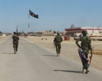 Iraqi troops advancing on a village near Ramadi, Iraq, with an Islamic State flag. The Islamic State's military setbacks in Iraq and Syria mean it will need to win victories elsewhere. Credit Osama Sami/Associated Press