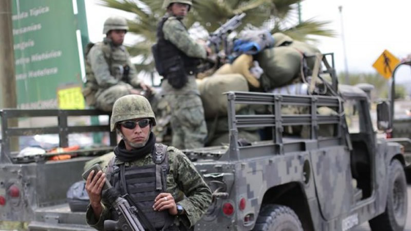Mexican soldiers stand guard outside Chilapa in the state of Guerrero, a combat zone for drug gangs, in May 2015. (Pedro Pardo / AFP/Getty Images)
