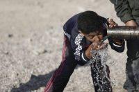 Un niño refugiado toma agua de una tubería en Idomeni, cerca la frontera de Grecia con Macedonia, el 20 de abril de 2016. KOSTAS TSIRONIS EFE