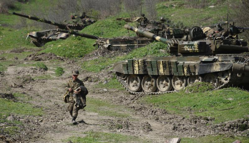 A soldier of the army of Nagorny Karabakh walks past tanks at a field position outside the village of Mataghis on 6 April 2016. Photo by Getty Images.