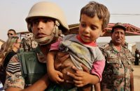 A Jordanian soldier carried a child newly arrived at the Rukban camp in September. Raad Adayleh/Associated Press