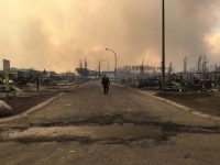 A police officer walking through a neighborhood destroyed by fire in Fort McMurray, Canada. Credit Rcmp/Agence France-Presse — Getty Images