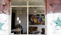A poster of Bashar al-Assad in an apartment block damaged in a car bomb attack near Sayyida Zeinab. Photo by Getty Images.