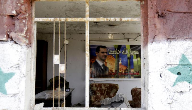 A poster of Bashar al-Assad in an apartment block damaged in a car bomb attack near Sayyida Zeinab. Photo by Getty Images. - See more at: https://www.chathamhouse.org/expert/comment/shift-syrian-constitution-could-help-assad-survive#sthash.S5eKCq9O.dpuf