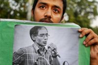A student with a portrait of the English professor A.F.M. Rezaul Karim Siddique, who was hacked to death on his way to work in April. Associated Press