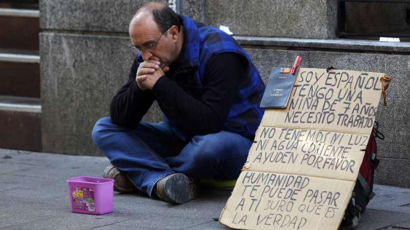 Un hombre pide ayuda en una céntrica calle de Madrid / SAMUEL SÁNCHEZ