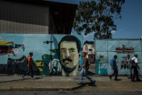 People walk past a mural of President Nicolás Maduro in Caracas. Meridith Kohut for The New York Times