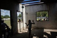 Children play in an abandoned structure by a soccer field in the Rivera Hernández neighborhood in San Pedro Sula, Honduras. Gangs used to frequent this building — a girl walking home from high school was kidnapped by gang members and then brought here and raped two years ago — and the soccer field used to be a place to bury bodies.