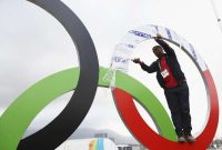 A worker helps install a set of Olympic Rings at the Olympic Park in Rio de Janeiro on Tuesday. (Ryan Pierse/Getty Images)