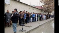 Men line up to vote outside a polling station in Kabul on April 5, 2014