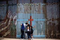 Una familia se comunica con parientes en Estados Unidos desde el lado mexicano de la frontera, en Tijuana. Guillermo Arias/Agence France-Presse — Getty Images