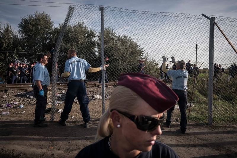 The Hungarian police standing guard this month along the border with Serbia as construction workers finished a border fence near Roszke, Hungary. Credit Sergey Ponomarev for The New York Times