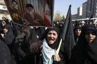 An Iranian woman holds a poster of Iranian Supreme Leader Ayatollah Ali Khamenei, and late revolutionary founder Ayatollah Khomeini, during an anti-Saudi protest rally in Tehran in 2015. (Vahid Salemi/Associated Press)